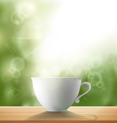 White cup standing on a wooden table in the garden vector
