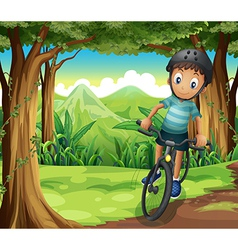 A boy biking in the middle of the forest vector
