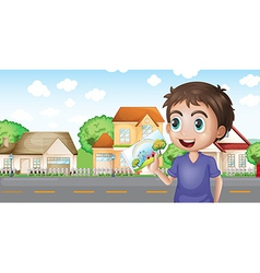 A boy holding a picture in front of the houses vector