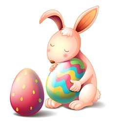 A rabbit hugging a colorful easter egg vector