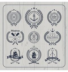 Vintage nautical wreath labels set on light wood vector