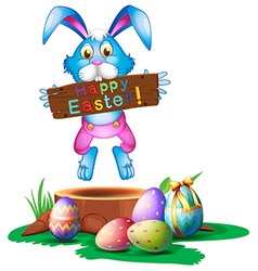 A rabbit holding an easter greeting vector