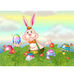 A rabbit with easter eggs in the garden vector