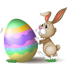 A bunny pushing an easter egg vector