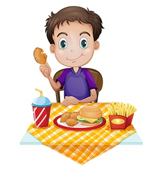 A young boy eating in a fastfood restaurant vector