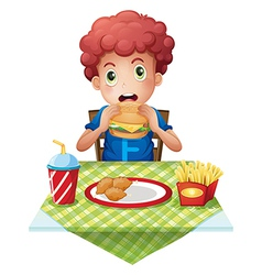 A curly-haired boy eating at a fastfood restaurant vector