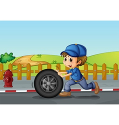 A boy wearing a hat pushing a wheel along the road vector