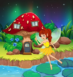 A fairy flying near the red mushroom house vector