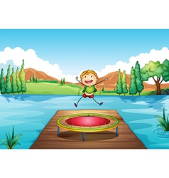 A boy playing with the trampoline at the river vector