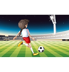 A girl playing soccer at the field vector