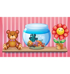 A shelf with a bear an aquarium and a toy flower vector