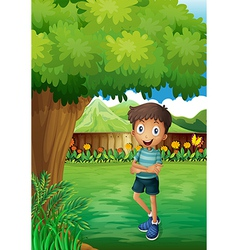 A smiling young man near the tree inside the gated vector