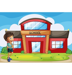A boy in front of the school building vector
