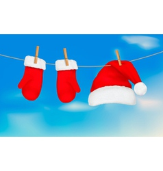 Santa hat and mittens hanging vector