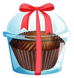 A cupcake inside a container with a red ribbon vector