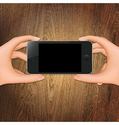 Wooden background with hands holding phone vector