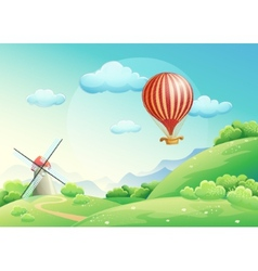 Summer fields with a mill and a balloon in the s vector