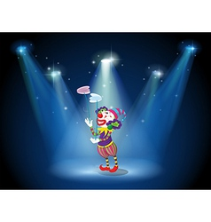 A clown performing on a stage under the spotlights vector