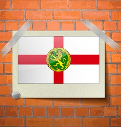 Flags alderney scotch taped to a red brick wall vector