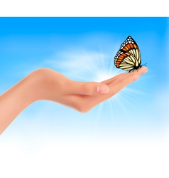Hand holding a butterfly against a blue sky vector