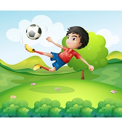 A boy kicking the soccer ball at the hilltop vector
