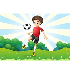A boy practicing soccer at the hilltop vector