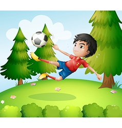 A boy playing soccer near the pine trees vector