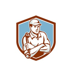 Mechanic holding spanner arms crossed shield vector