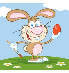 Brown easter bunny painting an egg outdoors vector
