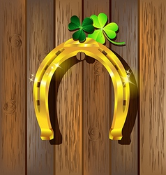 Gold horseshoe with shamrock on wooden vector
