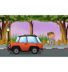A boy with his tools near the orange vehicle vector