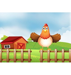 A hen above the fence with a wooden house at the vector