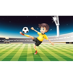 A boy in his yellow uniform playing soccer at the vector