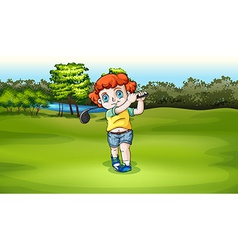 A young boy playing golf at the field vector