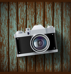 Old film camera lying on a wooden surface vector