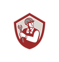 Mechanic holding wrench shield crest retro vector