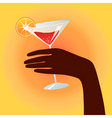 Hand holding a cocktail glass vector