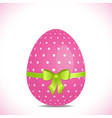Pink polka dot easter egg with green ribbon vector