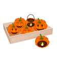 A pile of jack-o-lantern pumpkins in wooden box vector