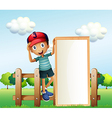 A boy standing at the fence wearing a cap holding vector