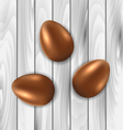 Easter chocolate three eggs on grey wooden vector