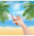 Hand holding a glass on the beach vector