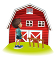 A boy standing in front of the red farmhouse vector
