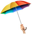 Hand with a rainbow umbrella vector