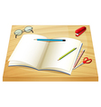 A table with an empty notebook pencils stapler and vector