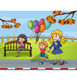 Two girls with a kid holding a balloon in the park vector