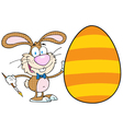 Happy bunny painting an easter egg vector