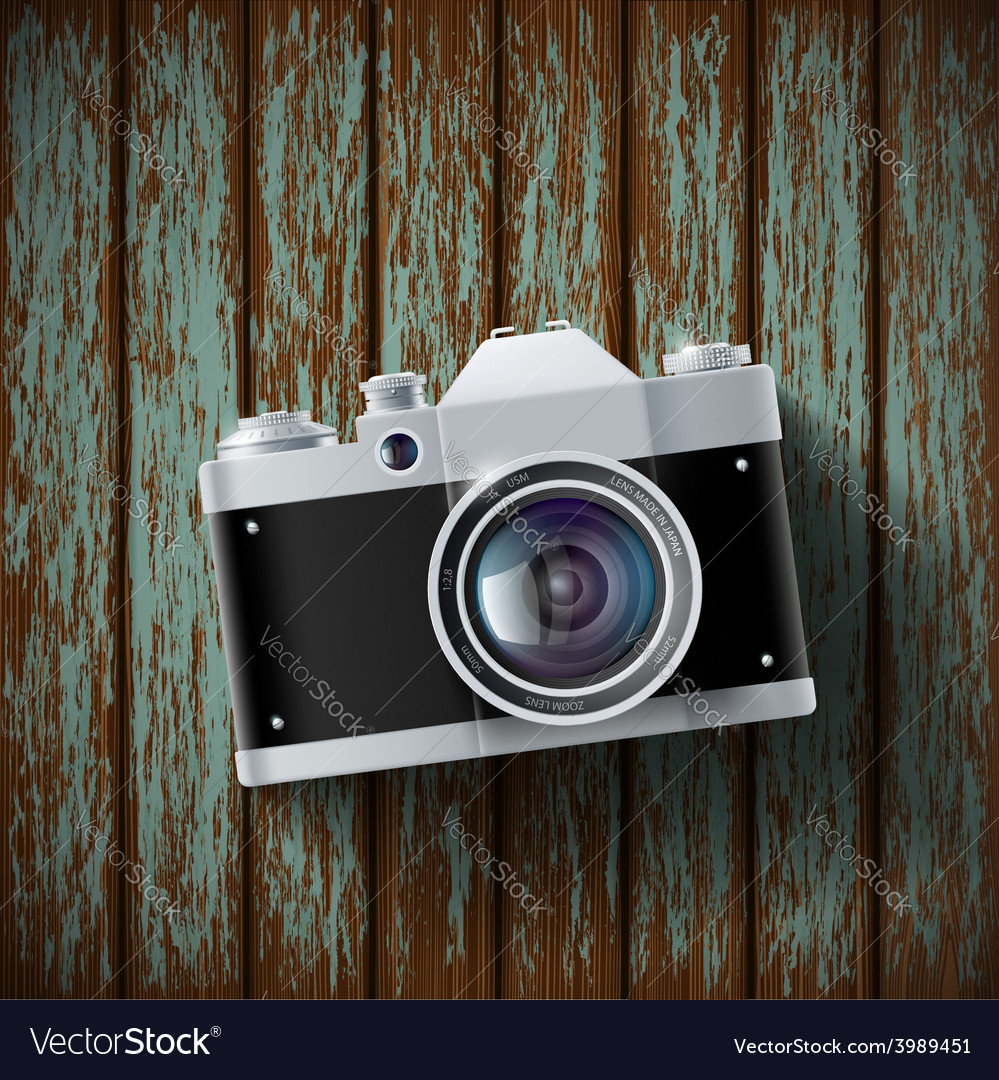 Old film camera lying on a wooden surface vector | Price: 1 Credit (USD $1)