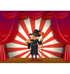 A scary witch holding a stick at the stage vector