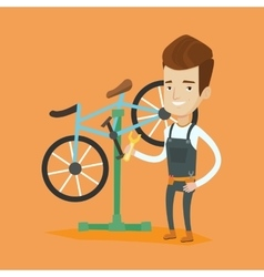 Caucasian bicycle mechanic working in repair shop vector